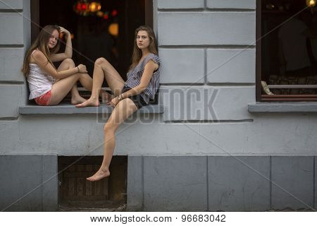 Two cute young girls sitting on the windowsill the night club at evening time.
