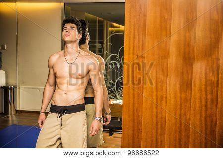 Muscular shirtless young man resting in gym