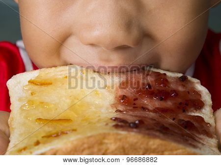 Asian Boy Bites White Bread With Orange Marmalade Strawberry Jam