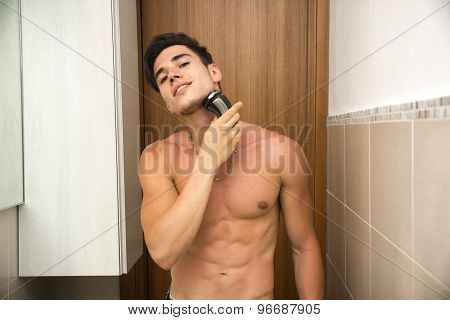 Muscular man shirtless using electric shaver, looking at camera