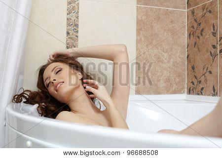 Fair-haired woman enjoying relaxation in bathroom