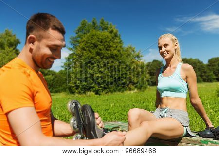 fitness, sport, summer, couple and healthy lifestyle concept - happy man helping woman to put on rollerblades outdoors