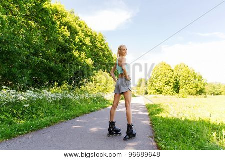 fitness, sport, summer, rollerblading and healthy lifestyle concept - happy young woman in rollerblades riding outdoors