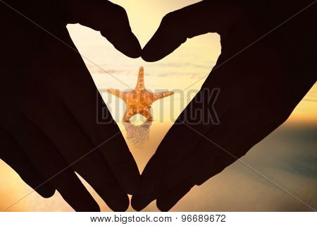 Woman making heart shape with hands against starfish on the sand