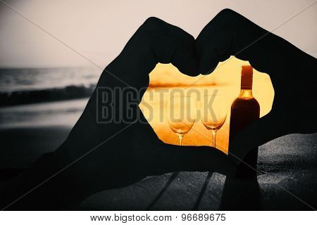 Couple making heart shape with hands against bottle of vine with two glass
