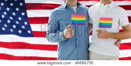 people, homosexuality, same-sex marriage, gay and love concept - close up of happy male gay couple hugging and holding rainbow flags over american flag background