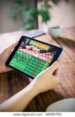 Woman using tablet pc against gambling app screen