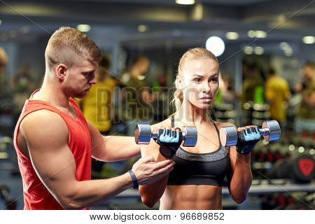 fitness, sport, bodybuilding and weightlifting concept - young woman and personal trainer with dumbbells flexing muscles in gym