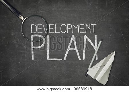 Development plan concept on black blackboard with empty paper sheet