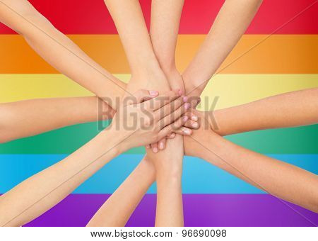 people, gesture, gay pride and homosexual concept - close up of women hands on top of each other over rainbow flag stripes background