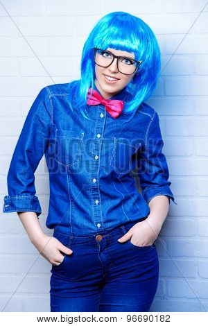 Modern girl wearing bright blue wig and jeans clothes posing by the urban white brick wall. Beauty, fashion.