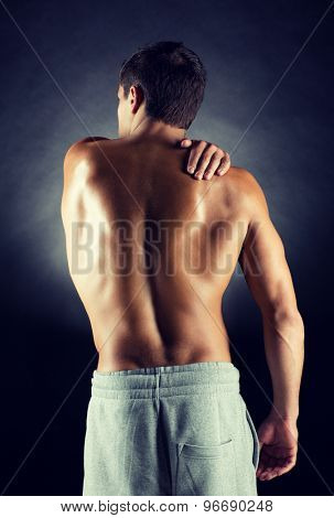 pain relief, sport, bodybuilding, strength and people concept - young man standing over black background