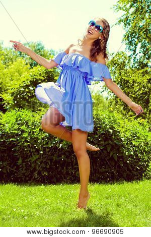Full length portrait of a happy beautiful girl in light summer dress walking in the summer park. Beauty, fashion. Holidays.