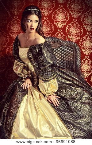 Full length portrait of a beautiful elegant lady in the lush expensive dress posing over vintage background. Renaissance. Barocco. Fashion.