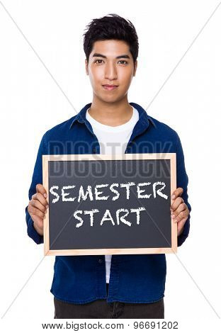 Indian man with chalkboard showing phrases of semester start