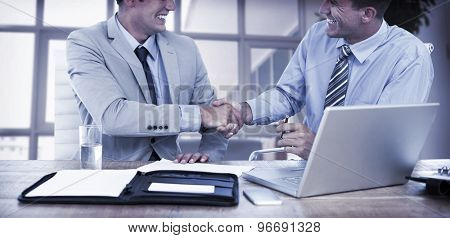 Business partners shaking hands in the office