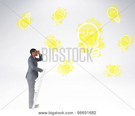 Businessman standing on ladder looking against grey background