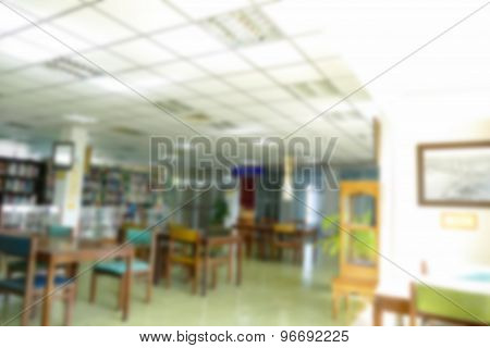 Blurry Defocused Image Of Book Shelf, Wooden Desk And Chair For Reading Book In The Library