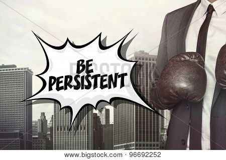 Be persistent text with businessman wearing boxing gloves
