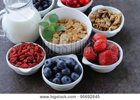 set of ingredients for a healthy food breakfast - muesli, fresh and dried fruit, nuts, goji berries