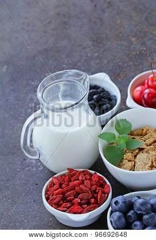 set of ingredients for a healthy food breakfast - muesli, fresh and dried fruit, nuts, goji berries