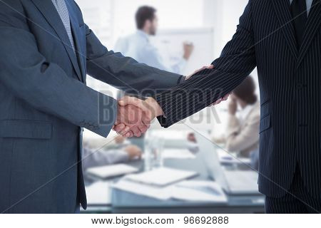 Handshake in agreement against young business people in board room meeting
