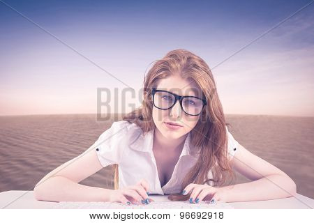 Pretty redhead typing on keyboard against desert scene
