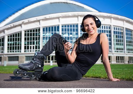 Happy Woman In Roller Skates Sitting And Listening Music