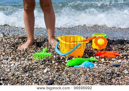 Child's legs and toys on the beach