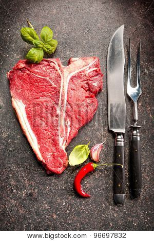 Raw fresh meat T-bone steak and seasoning on dark background
