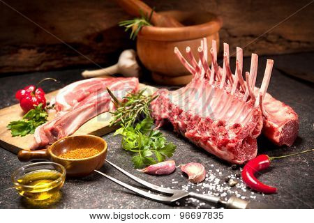 Racks of lamb ready for cooking on dark background
