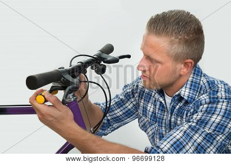 Man Tightening Bolt Of Bicycle Wheel