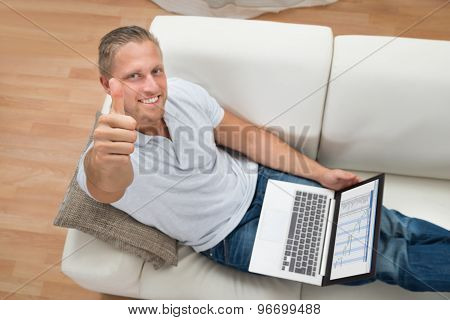 Man Showing Thumb Up While Working On Laptop