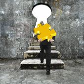 pic of keyhole  - Man carrying golden jigsaw puzzle climbing old concrete stairs toward keyhole with blank white view - JPG