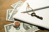 picture of memento  - Opened notebook with a blank sheet pencil key and money on the old tissue - JPG