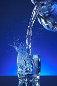 Постер, плакат: Water splash poured into a glass blue background refreshing freshness and health Water bottle
