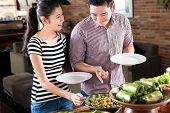 stock photo of buffet  - Asian woman and man choosing food at Indonesian buffet in restaurant - JPG