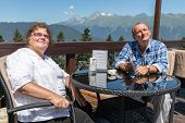 picture of mountain chain  - elderly couple at a table on the balcony in the mountains - JPG