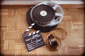 picture of mm  - Cinema movie clapper board and 35 mm film reel on wooden floor vintage color effect - JPG