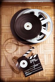 pic of mm  - Cinema movie clapper board and 35 mm film reel on wooden floor vintage color effect vertical frame - JPG