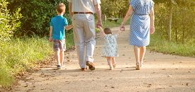 picture of grandparent child  - Closeup of grandparents and grandchildren walking on a nature path - JPG