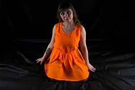 stock photo of curvy  - Photo of curvy woman in orange dress on black background - JPG