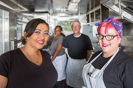 stock photo of food truck  - Crew of four working inside a modern food truck - JPG