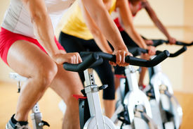 stock photo of exercise bike  - Three people in the gym - JPG