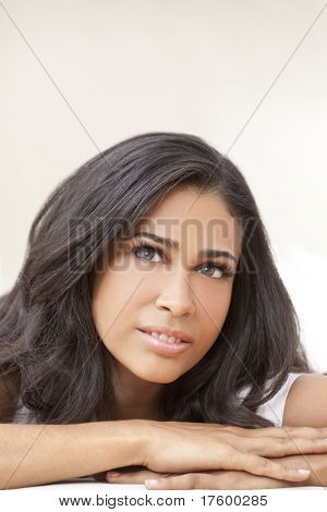 Studio portrait of a beautiful young Latina Hispanic young woman or girl looking thoughtful resting on her hands