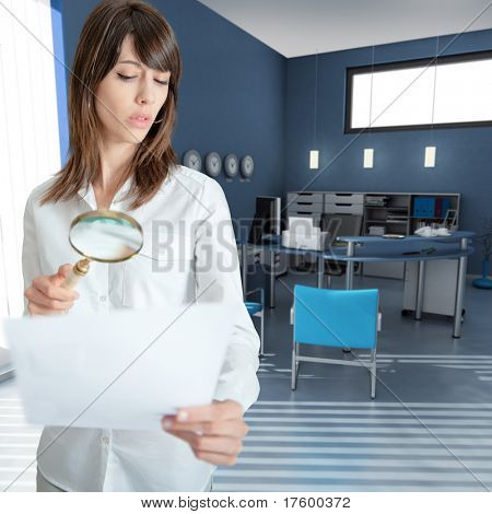 Young woman inspecting a document through a magnifying glass in an office