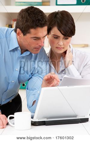 Worried Couple Working From Home Using Laptop