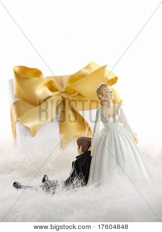 Wedding cake figures with gold ribbon gift on white