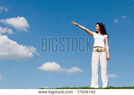 young woman on a green meadow and show something