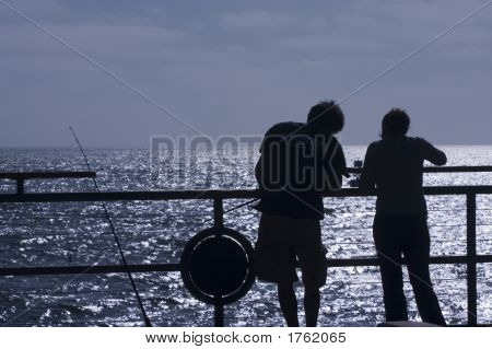 Young Couple Fishing Off The Pier 1
